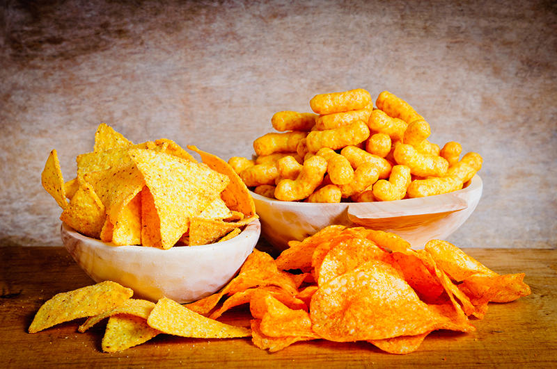 Chips, nachos and curls snacks on a wooden background