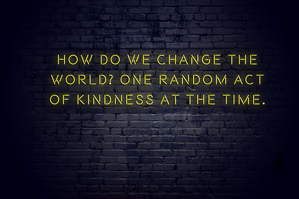 Neon sign with positive wise motivational quote about random acts of kindness against brick wall.